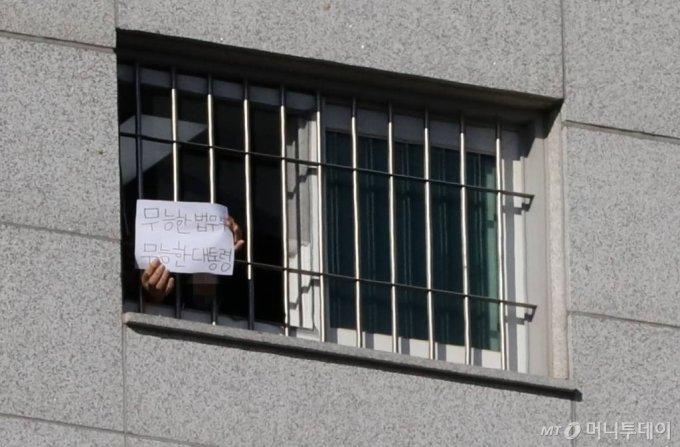 [서울=뉴시스]고범준 기자 = 서울동부구치소에 대한 6차 전수검사에서 수용자 66명이 추가로 신종 코로나바이러스 감염증(코로나19) 확진 판정을 받아 누적 확진자가 현재까지 1,161명으로 집계된 6일 서울 송파구 서울동부구치소에서 한 수용자가 종이에 쓴 글을 취재진에게 보여주고 있다. 내용은 '무능한 법무부 무능한 대통령'이라고 적혀있다. 2021.01.06. bjko@newsis.com