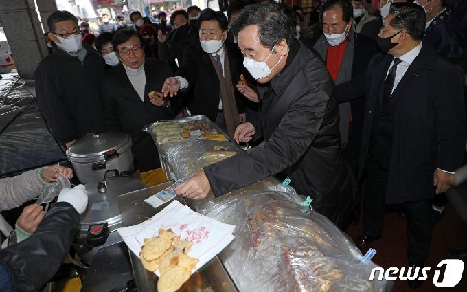 이낙연 더불어민주당 대표가 광주를 찾아 18일 오후 광주 서구 양동시장에서 붕어빵을 사먹은 후 전통시장에서 사용 가능한 온누리상품권으로 계산을 하고 있다.2021.1.18/뉴스1 © News1 허단비 기자