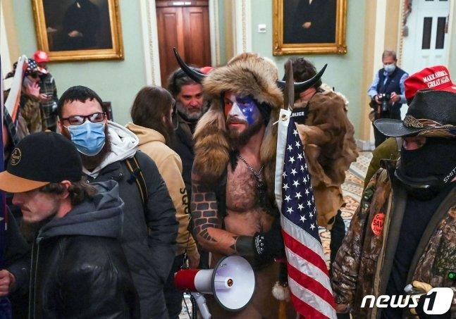 지난 6일 미 연방의회 의사당에 난입한 도널드 트럼프 대통령의 지지자 제이컵 챈슬리(가운데) /AFP=뉴스1