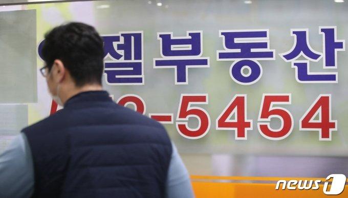 18일 오후 서울 시내의 공인중개사 사무소 앞을 한 시민이 지나고 있다. /사진=뉴스1