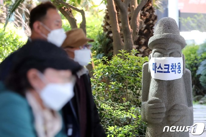 제주국제공항에 도착한 관광객들이 마스크를 쓴 돌하르방 앞을 지나가고 있다.2020.4.28 /뉴스1 © News1 오현지 기자