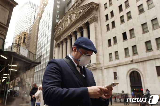 뉴욕 증권거래소 앞에서 한 남자가 스마트폰을 보고 있다.© 로이터=뉴스1