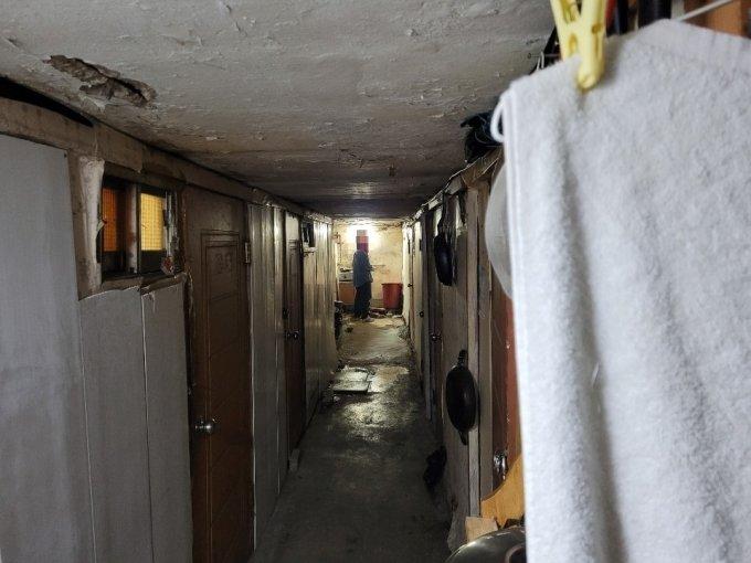 19일 동자동 쪽방촌의 한 '쪽방 건물'에서 주민 김모씨가 공용주방을 사용하는 모습./사진 = 오진영 기자