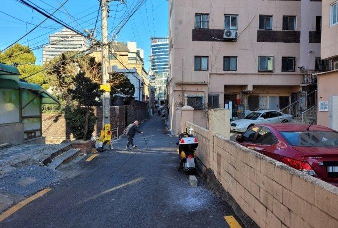 19일 동자동 골목에서 김모씨(83)가 지팡이를 짚은 채 걷는 모습 / 사진 = 오진영 기자