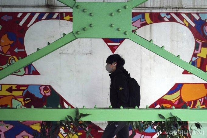 """[도쿄=AP/뉴시스]18일 코로나19 확산 예방을 위해 마스크를 쓴 한 남성이 도쿄 시부야 지역의 다리 밑을 걸어가고 있다. 도쿄에서 월요일 1200명 이상의 코로나19 신규 확진자가 발생해 확산 속도가 줄지 않는 가운데 7월 예정인 도쿄올림픽·패럴림픽에 대한 회의론이 다시 확산하고 있다. 스가 총리는 이날 시정연설에서 """"대책에 만전을 기해 대회를 실현하겠다는 결의로 준비하겠다""""라고 밝혔다. 2021.01.18."""