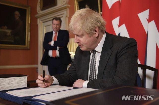 [런던=AP/뉴시스]보리스 존슨 영국 총리가 30일(현지시간) 런던 총리 관저에서 데이비드 프로스트(왼쪽) 영국 통상교섭본부장이 지켜보는 가운데 브렉시트(영국의 유럽연합 탈퇴) 관련 미래관계 협정 합의안에 서명하고 있다. 2020.12.31.