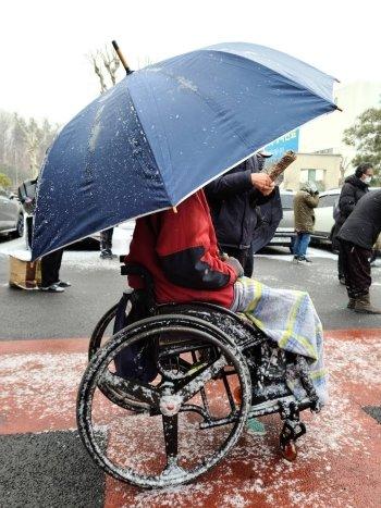 안나의 집에서 만든 도시락을 받기 위해 우산을 쓰고 휠체어를 탄 채 기다리는 노숙인./사진=김하종 신부 페이스북