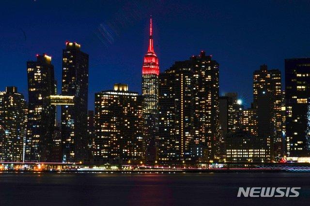 뉴욕=AP뉴시스/ 19일(현지시간) 미국 뉴욕의 엠파이어 스테이트 빌딩 꼭대기에 코로나19 희생자를 추모하는 붉은색 조명이 켜져 있다. 2021.01.20.