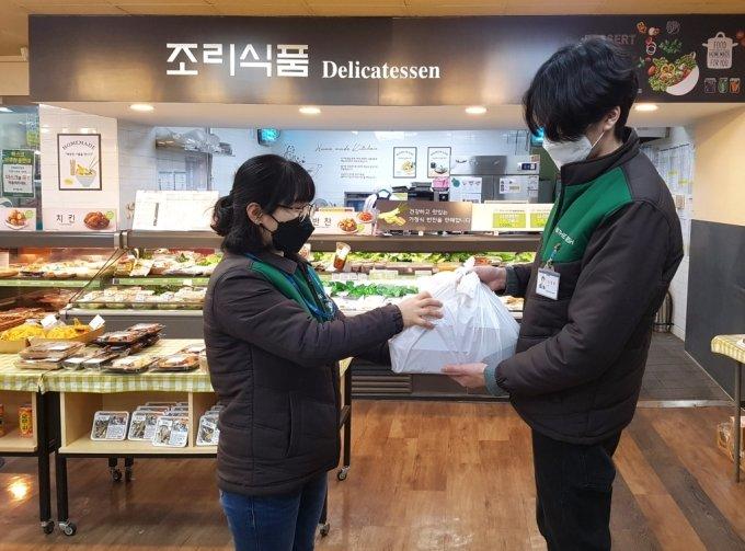 GS더프레시 직원이 주문 들어온 상품을 배송직원에게 전달하고 있다 /사진= GS수퍼마켓 제공