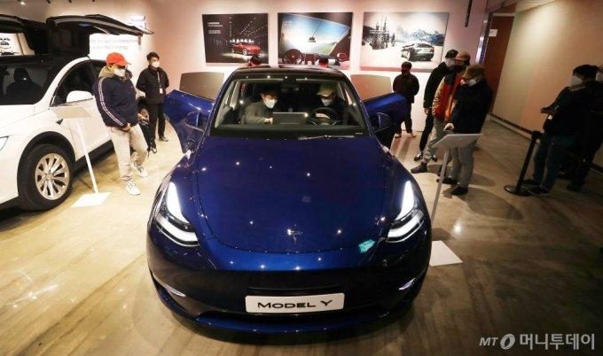 테슬라 코리아가 13일 서울 영등포구 롯데백화점 영등포점에서 '모델 Y'를 국내 최초공개한 가운데 시민들이 차량을 살펴보고 있다. / 사진=김휘선 기자 hwijpg@