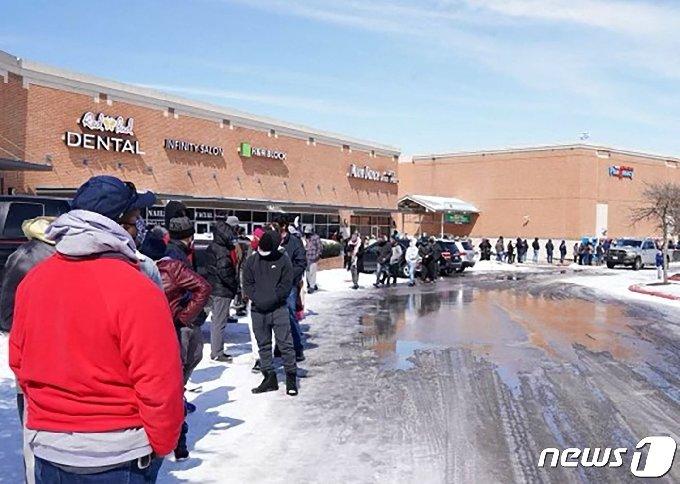 16일(현지시간) 겨울 폭풍으로 대규모 정전사태가 벌어진 미국 텍사스주 한 쇼핑몰 앞에서 사람들이 줄을 서서 기다리고 있다. © AFP=뉴스1