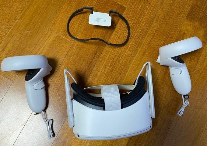 오큘러스 퀘스트2 컨트롤러 2개와 헤드셋. 위엔 안경을 쓰는 사람을 위한 보조도구가 있다.