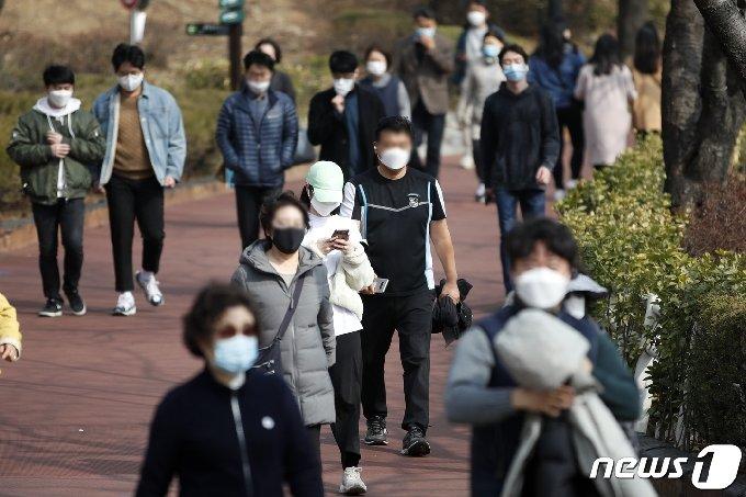 서울 낮 최고기온이 12도로 예보된 22일 오후 서울 송파구 석촌호수에서 시민들이 산책을 하고 있다. 2021.2.22/뉴스1 © News1 이승배 기자