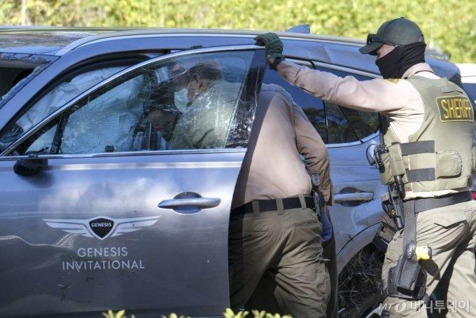[로스앤젤레스=AP/뉴시스]미 프로골퍼 타이거 우즈가 타고 있던 차량이 23일(현지시간) 미 캘리포니아주 로스앤젤레스 카운티 란초 팔로스 베르데스 인근에서 전복돼 한 경찰관이 사고 차량인 제네시스 GV80을 살펴보고 있다. 우즈는 이 사고로 다리를 다쳐 병원으로 이송돼 수술을 받고 있다고 그의 매니저 마크 스타인버그가 밝혔다. 2021.02.24.