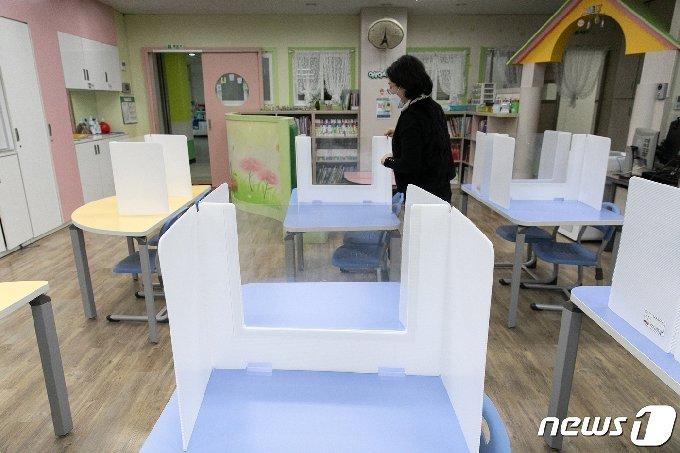 2021학년도 새학기 개학을 일주일가량 앞둔 지난 23일 서울의 한 초등학교 돌봄교실에서 교직원이 칸막이를 정리하고 있다./뉴스1 © News1 이승배 기자