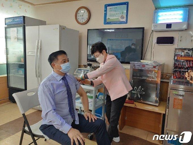 배용정 금산효사랑이사장이 금산 첫번째 접종자로 코로나19 예방 백신을 맞고 있다.(금산군 제공)© 뉴스1