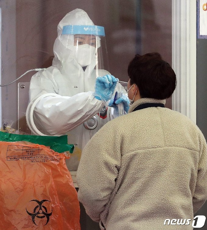 27일 오전 서울역 광장에 마련된 신종 코로나바이러스 감염증(코로나19) 임시선별진료소에서 의료진이 시민의 검체를 채취하고 있다. 질병관리청 중앙방역대책본부에 따르면 이날 0시 기준 코로나19 누적 확진자는 415명 증가한 8만932명으로 나타났다. 사망자는 10명 늘어 1595명으로 집계 됐다. 신규 확진자 415명 중 지역발생 사례는 405명, 해외유입 사례는 국내 입국자 검역 3명 포함 10명이다. 2021.2.27/뉴스1 © News1 김진환 기자