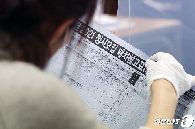 한 학부모가 수능배치참고표를 살펴보고 있다.  © News1