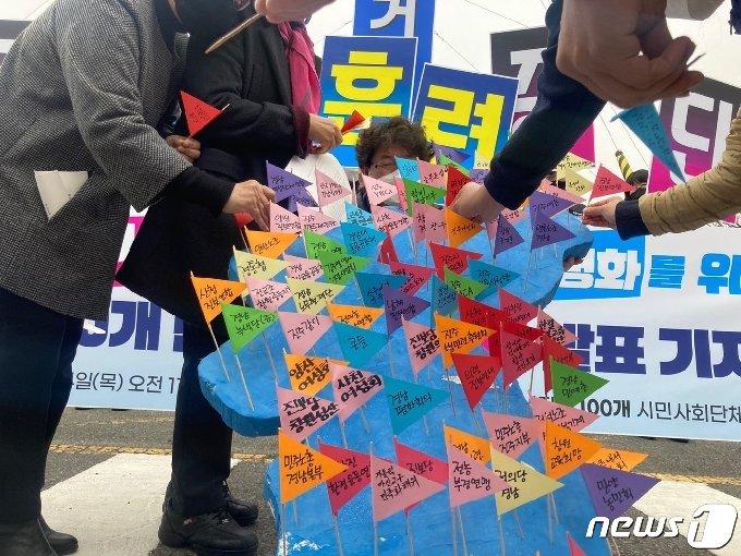 경남 도내 100개 단체는 4일 열린 기자회견을 위해 퍼포먼스를 준비했다. 100개 단체의 이름이 쓰인 깃발을 한반도 모형 위에 꽂으면서 평화를 기원하고 있다. © 뉴스1 김다솜 기자