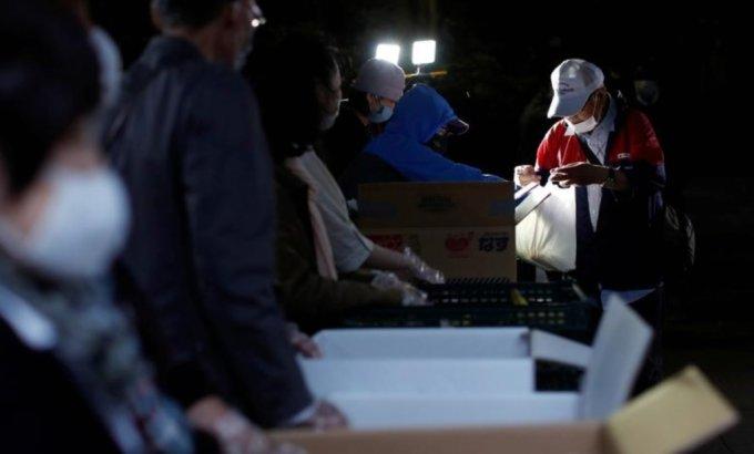 2020년 5월 9일 일본 도쿄에서 COVID-19 확산이 계속되고 있는 가운데 한 노인이 식량지원을 받고 있다. /사진=로이터