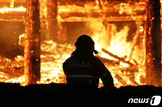 5일 오후 6시 50분께 전북 정읍시 내장사 대웅전에서 방화로 추정되는 화재가 발생해 불길이 치솟고 있다. 한 소방관이 불길을 잡기 위해 안간힘을 쓰고 있다.(정읍시 제공) 2021.3.5/뉴스1 © News1 박제철 기자