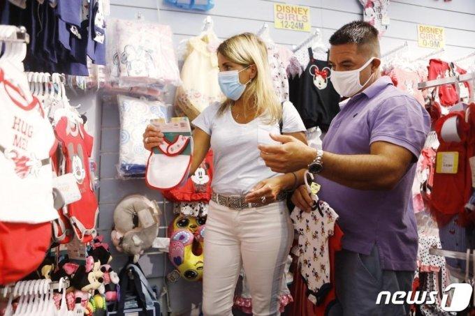 (레이크부에나비스타 AFP=뉴스1) 우동명 기자 = 8일(현지시간) 플로리다주 레이크부에나비스타에 있는 디즈니 월드의 선물가게에서 마스크를 쓴 쇼핑객들이 물건을 고르고 있다.   ⓒ AFP=뉴스1