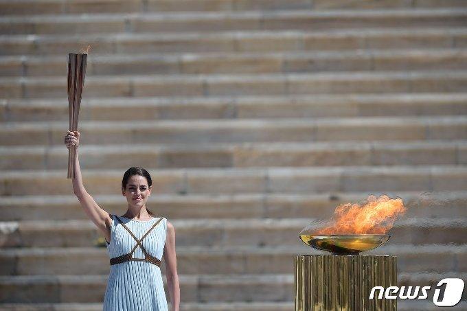 그리스 배우 산티 게오르기오가 19일 (현지시간) 아테네에서 열린 도쿄 올림픽 성화 인수식에서 성화를 들고 있다. © AFP=뉴스1 © News1 우동명 기자