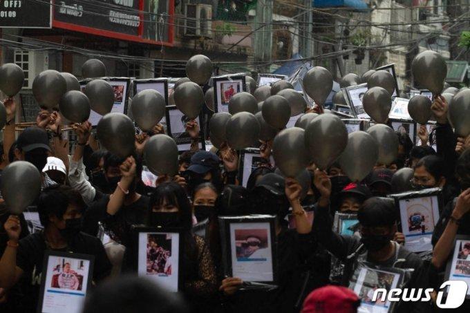 (양곤 AFP=뉴스1) 우동명 기자 = 5일(현지시간) 미얀마 양곤에서 군부 쿠데타를 규탄하는 시위대가 시위 중 숨진 시민의 사진과 가면을 들고 시위를 하고 있다.  (C) AFP=뉴스1