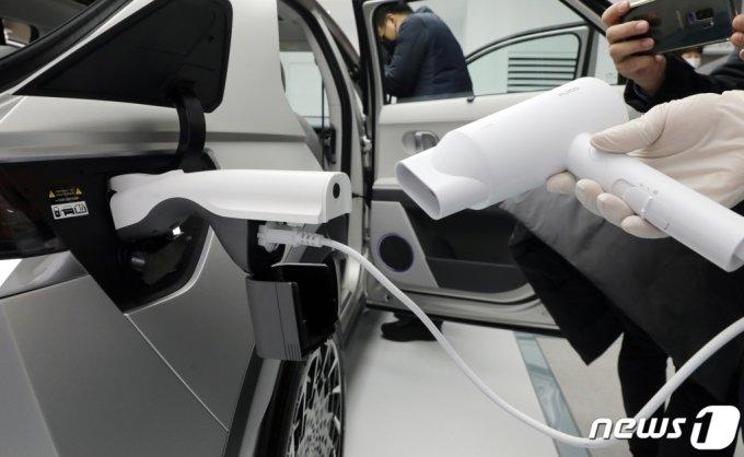 (서울=뉴스1) 김진환 기자 = 현대자동차가 첫 전용 전기차 '아이오닉5'를 공개했다.    현대자동차의 첫 전용 전기차 '아이오닉 5'는 현대차그룹이 처음으로 개발한 전기차 전용 플랫폼 'E-GMP'가 적용돼 1회 충전으로 450km를 주행할 수 있는 등 최신 신기술로 국내외에서 폭발적인 관심을 받고 있다.   사진은 지난 17일 서울 용산구 현대자동차 원효로 사옥에 전시된 아이오닉5에서 일반 전기제품을 연결해 시연하는 모습. 2021.3.19/뉴스1