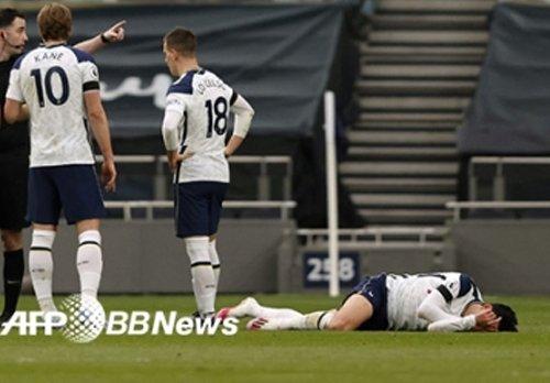 손흥민(오른쪽)이 지난 12일 영국 런던에서 열린 맨체스터 유나이티드와의 경기에서 스콧 맥토미니가 휘두른 팔에 얼굴을 가격당한 뒤 쓰러져 있는 모습. /AFPBBNews=뉴스1