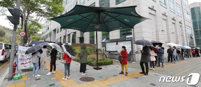 12일 서울 중랑구 보건소에 마련된 선별진료소를 찾은 시민들이 신종 코로나 바이러스 감염증(코로나19) 검사를 받기 위해 줄지어 기다리고 있다. 중앙방역대책본부는 이날 0시 기준으로 코로나19 신규 확진자가 587명 늘어 누적 11만146명이라고 밝혔다. 2021.4.12/뉴스1 © News1 박지혜 기자