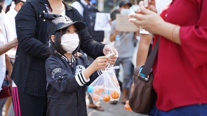 지난 2월 미얀마 양곤 시내에서 군부의 쿠데타 반대 시위에 참가한 시민에게 간식을 건네는 어린이. 사진제공=김빛솔씨.© 뉴스1