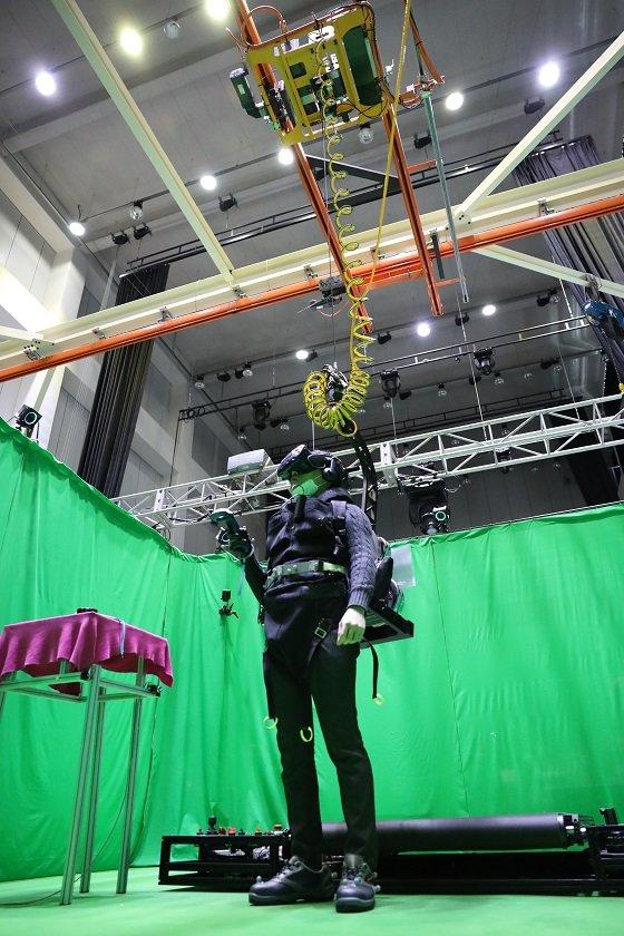 햅틱슈트를 입고 와이어 장비에 연결된 혼합현실 플랫폼을 체험하고 있는 모습/사진=한국생산기술연구원