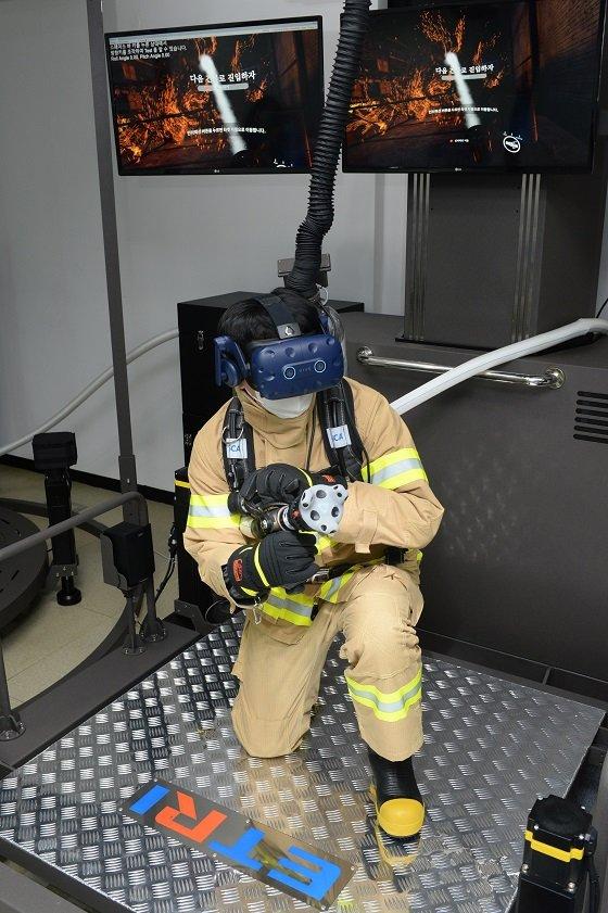 ETRI 연구진이 개발한 시뮬레이터를 통해 VR 소방훈련을 진행하는 모습/사진=ETRI