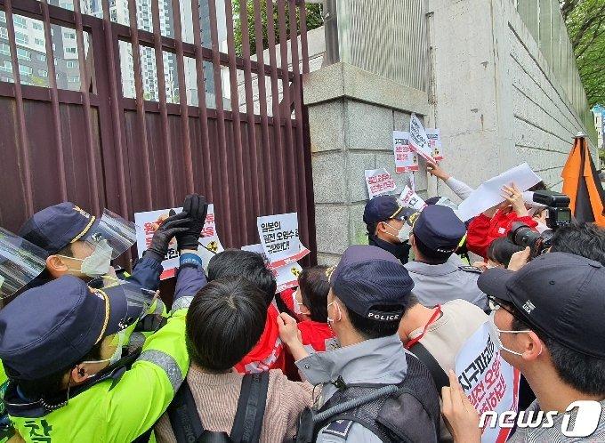 진보당 부산시당이 15일 오후 동구 일본영사관 벽에 항의 스티커를 부착하고 있다. 이 과정에서 경찰과의 물리적 충돌이 빚어지기도 했다.2021.4.15/© 뉴스1 노경민 기자