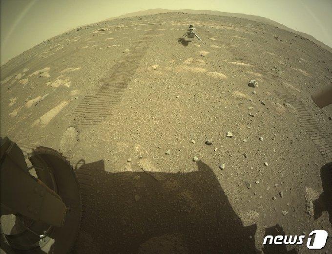 4일(현지시간) 미국 NASA의 화성 탐사 로버 '퍼서비어런스'에서 분리된 헬리콥터 '인저뉴어티'가 화성 표면에 안착한 모습이 보인다. © AFP=뉴스1 © News1 우동명 기자