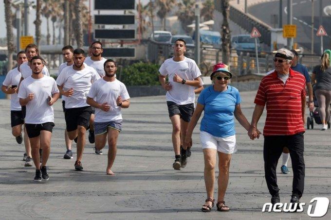 17일(현지시간) 이스라엘 텔아비브의 한 거리에서 마스크를 벗은 시민들이 운동을 하고 있다./사진=(AFP=뉴스1)