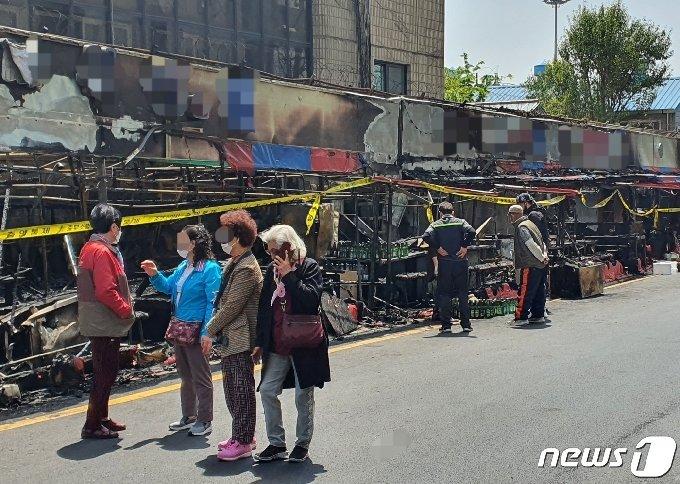 21일 부산 동구 풍물거리 포장마차촌 상인들이 불이 난 현장을 둘러보고 있다.2021.4.21 /© 뉴스1 노경민 기자