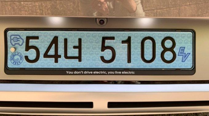 """현대차 아이오닉5의 번호판.  """"전기차를 타는 게 아니다, 전기차를 '사는' 것이다(You don't drive electric, You live electric)""""라는 문구가 적혀있다/사진=이강준 기자"""