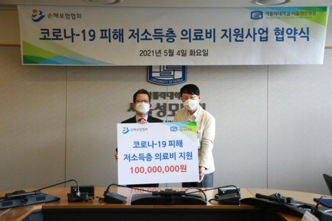 정지원 손해보험협회장(왼쪽)이 김용식 서울성모병원장(오른쪽)에게 의료비 지원금을 전달하고 있다./사진=손해보험협회