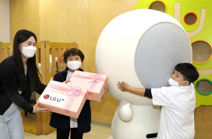 4일 한국백혈병소아암협회를 방문한 홀맨과 LG유플러스 임직원이 소아암 환아에게 선물을 전달하고 있다. /사진=LG유플러스