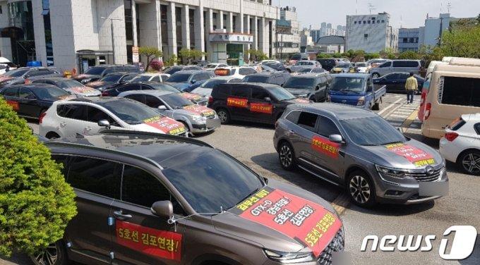 (김포=뉴스1) 정진욱 기자 = 인천 검단·김포 시민들이 1일 경기 김포시청 일대에서 GTX-D 강남 직결을 요구하는 차량 시위를 하고 있다. 시민들은 이날 차량 200여대를 동원해 시위를 했다. (김포검단시민교통연대제공)2021.5.1/뉴스1