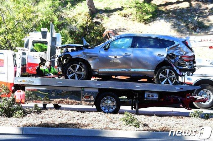 (AFP=뉴스1) = '골프 황제' 타이거 우즈가 탄 차량이 23일(현지시간) 캘리포니아주 로스앤젤레스의 란초 팔로스 베르데스 인근에서 전복된 뒤 옮겨지고 있다. 우즈는 병원으로 긴급 이송돼 다리 수술을 받은 것으로 알려졌다.  (C) AFP=뉴스1