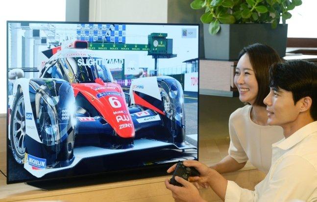 LG전자 모델이 48형 올레드 TV로 게임을 즐기며 제품을 소개하고 있다./사진제공=LG전자