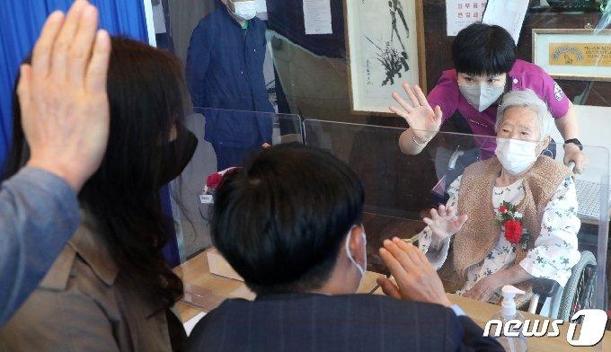 어버이날을 하루 앞둔 7일 전북 전주시 한솔요양병원에서 비접촉 면회를 하는 어머니 임순희(89)씨가 두 아들과 며느리에게 인사를 하고 있다. 2021.5.7/뉴스1 © News1 유경석 기자
