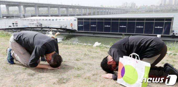 故 손정민 군의 아버지 손현씨(오른쪽)와 차종욱 민간구조사(오른쪽)가 어버이날인 8일 오후 서울 서초구 반포한강공원 택시승강장 앞에서 서로에게 절을 하고 있다. /사진= 뉴스1