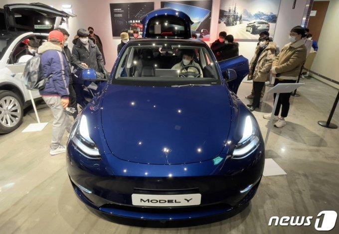 (서울=뉴스1) 김진환 기자 = 테슬라가 '모델Y'를 국내시장에 최초 공개했다. 테슬라가 새로 출시하는 중형 스포츠유틸리티차량(SUV) 모델Y는 3열 옵션으로 최대 7명이 탑승할 수 있는 차량이다. 1회 충전으로 505km 주행이 가능하고, 전용 고속충전기로 15분 충전하면 270km를 주행할 수 있다. 국내 판매 가격은 아직 정해지지 않았다. 사진은 13일 오전 서울 롯데백화점 영등포점에 전시된 테슬라 '모델Y'의 모습. 2021.1.13/뉴스1