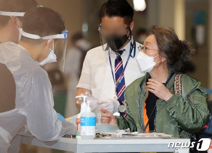입국 후  인천공항 육군 검역 지원단에게 입국 안내를 받고 있는 윤여정. 2021.5.8/뉴스1 © News1 김진환 기자
