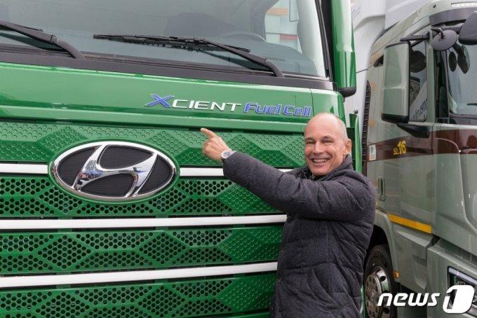 (서울=뉴스1) = 현대자동차는 7일(현지시간) 스위스 루체른에서 유럽으로 수출한 '엑시언트 수소전기트럭'을 스위스 주요 7개 마트·물류 기업에 인도했다.  이날 적재함 탑재 작업을 마친 차량 7대를 1차로 인도했으며, 10월 말 3대를 추가로 인도할 예정이다.  이후 현대차는 올해 말까지 수소전기트럭 총 40대를 스위스에 추가 수출할 예정이다. 스위스 정부는 수소 시장 활성화를 위해 스위스 각 지역에 100개의 수소충전소를 설치할 계획이다. 사진은 현대자동차 '엑시언트 수소전기트럭' 차량 앞에서 스위스 고객사 트라베고(Travego) 관계자가 기뻐하는 모습. (현대차 제공) 2020.10.8/뉴스1