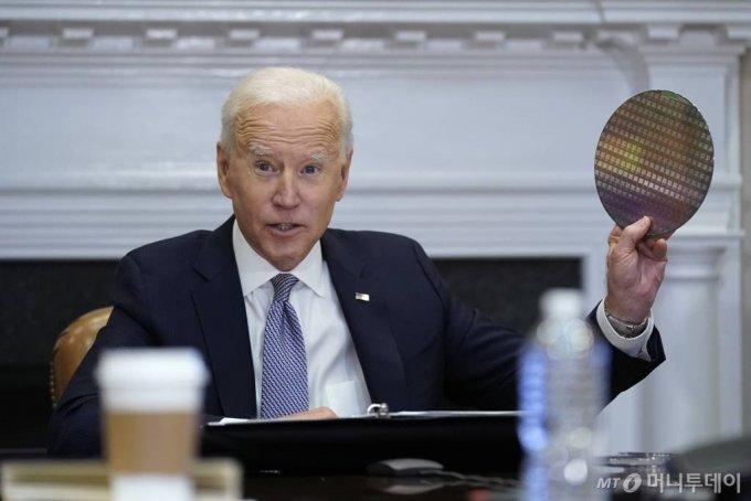 조 바이든 미국 대통령이 지난 4월12일(현지시간) 미국 워싱턴 백악관 루즈벨트룸에서 열린 반도체 공급망 복원에 관한 최고경영자(CEO) 화상 회의에 참석해 실리콘 웨이퍼를 들고 있다. /사진=뉴스1